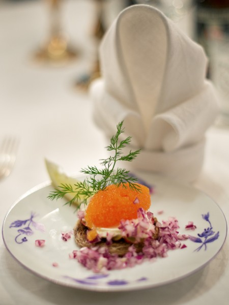 Vendace roe toast with a thin slice of apple and diced red onion